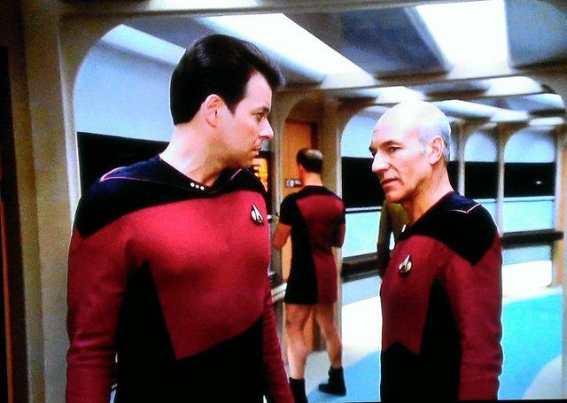 新スタートレックのシーズン1の第25話、ピカード艦長とライカー副長が廊下で話してる背景に立っている男性乗組員
